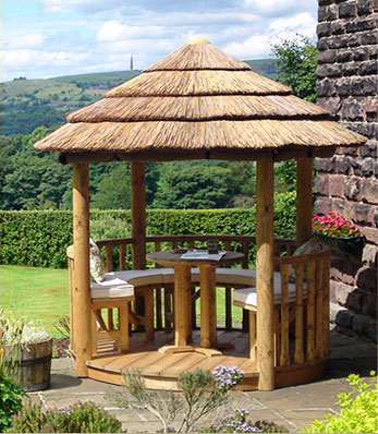 2 metre spindle thatched garden summerhouse with fields and hills in the distance