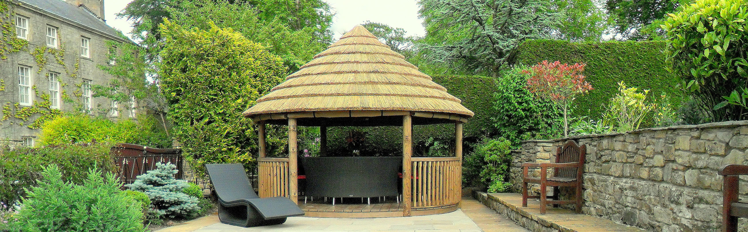 Wide shot of 4 metre gazebo on patio with foliage behind