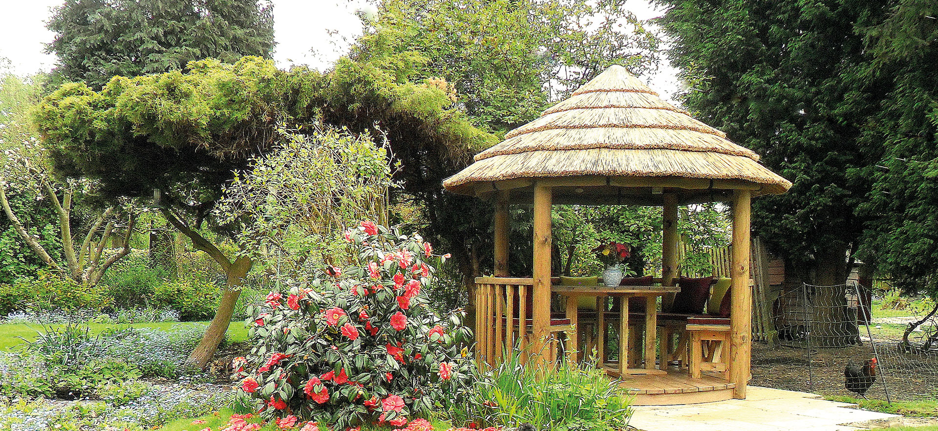 2.5 metre thatched gazebo next to floral foliage