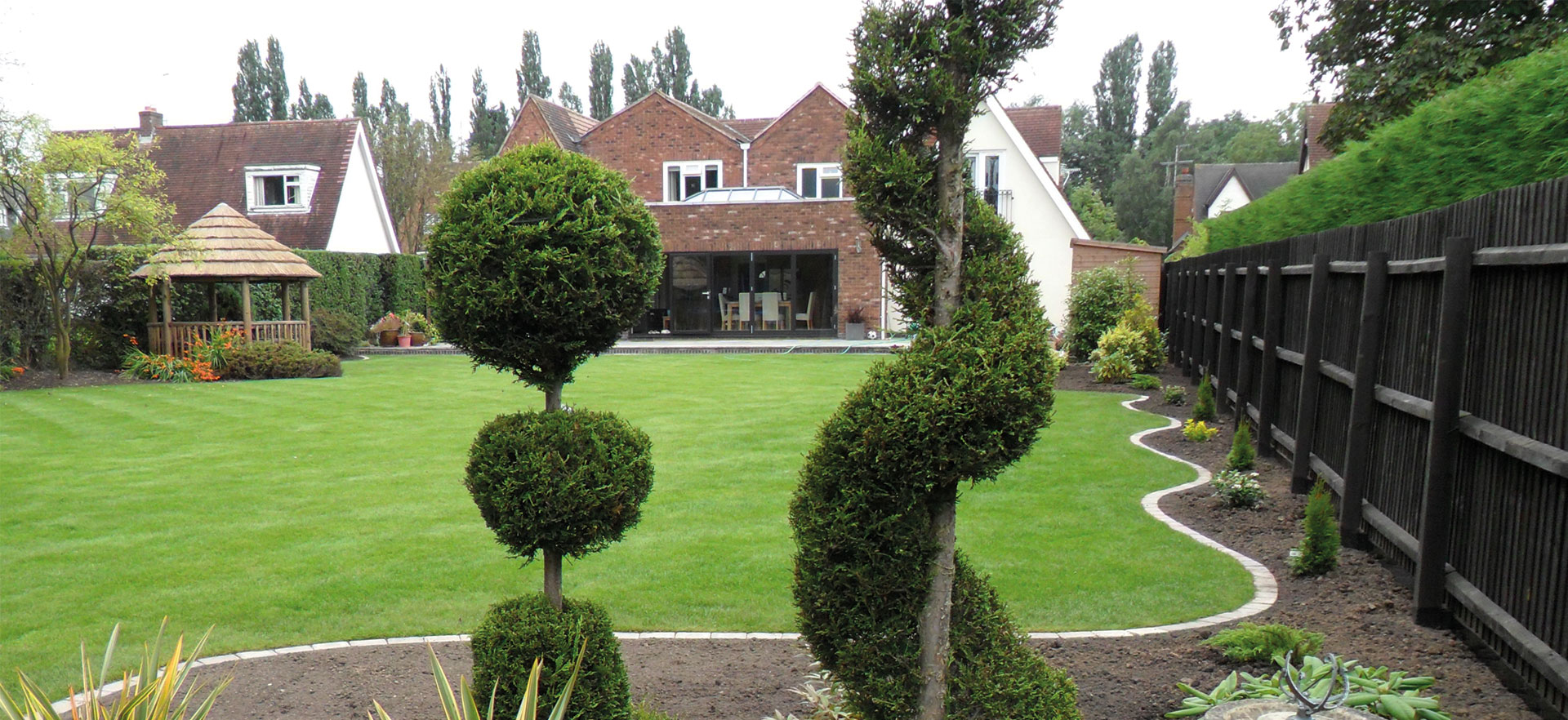 wide shot of large garden with 3 metre thatched gazebo to the side