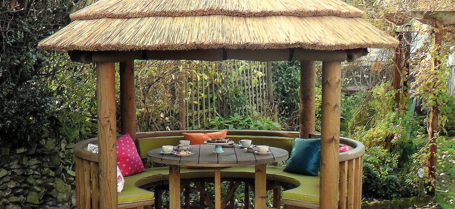 3 metre thatched gazebo in enclosed garden surrounded by foliage