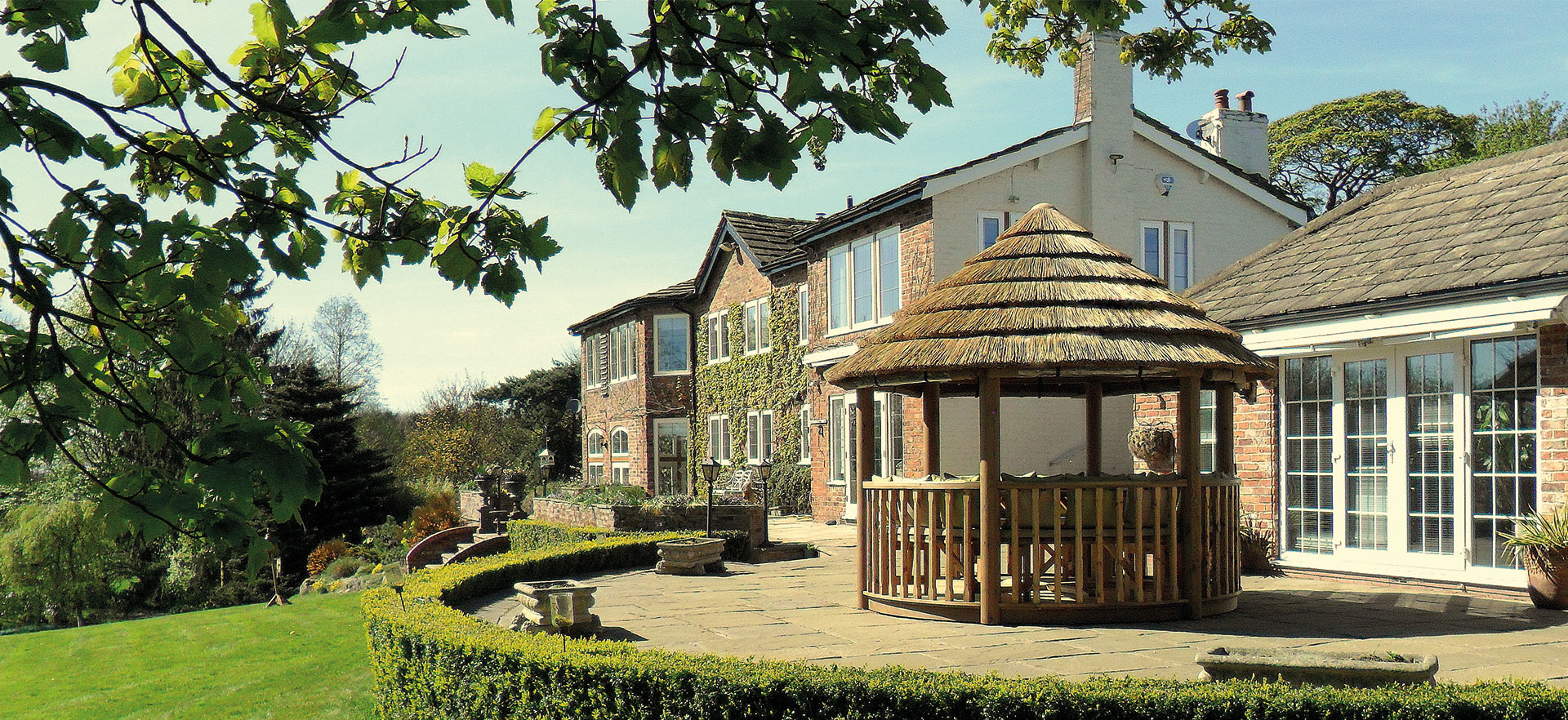 3 metre thatched gazebo on patio of large house