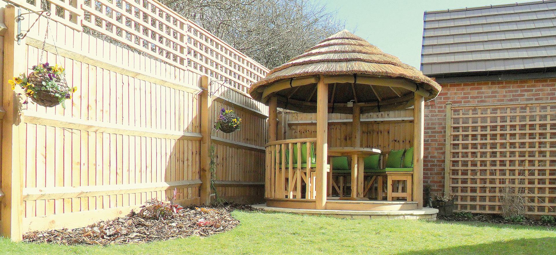 2.5 metre thatched garden gazebo in corner of garden next to fencing