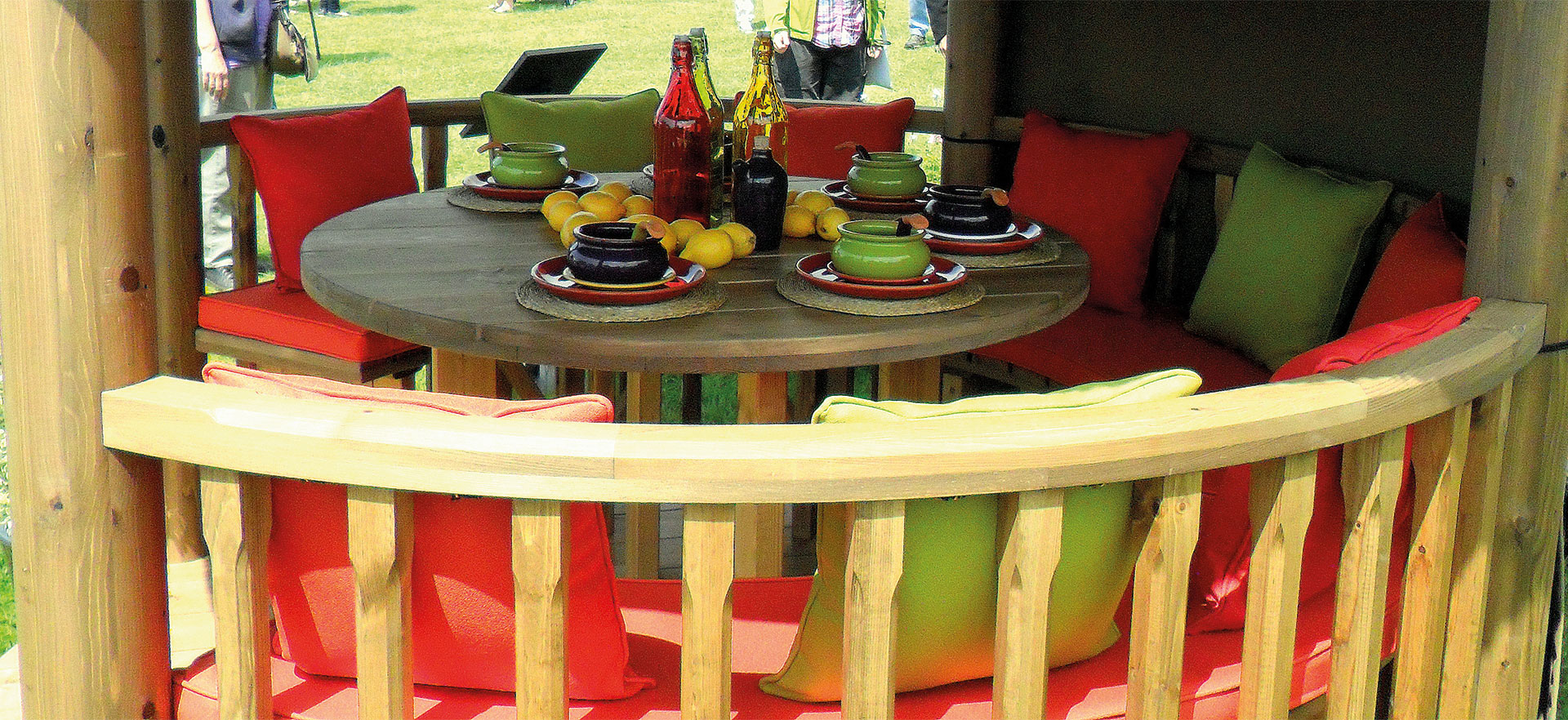 Close up of the inside of a 2.5 metre gazebo with red and green pillows and table decoration