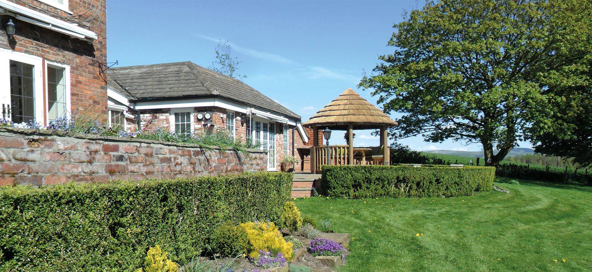 Image looking up at 3 metre gazebo on patio in front of large house