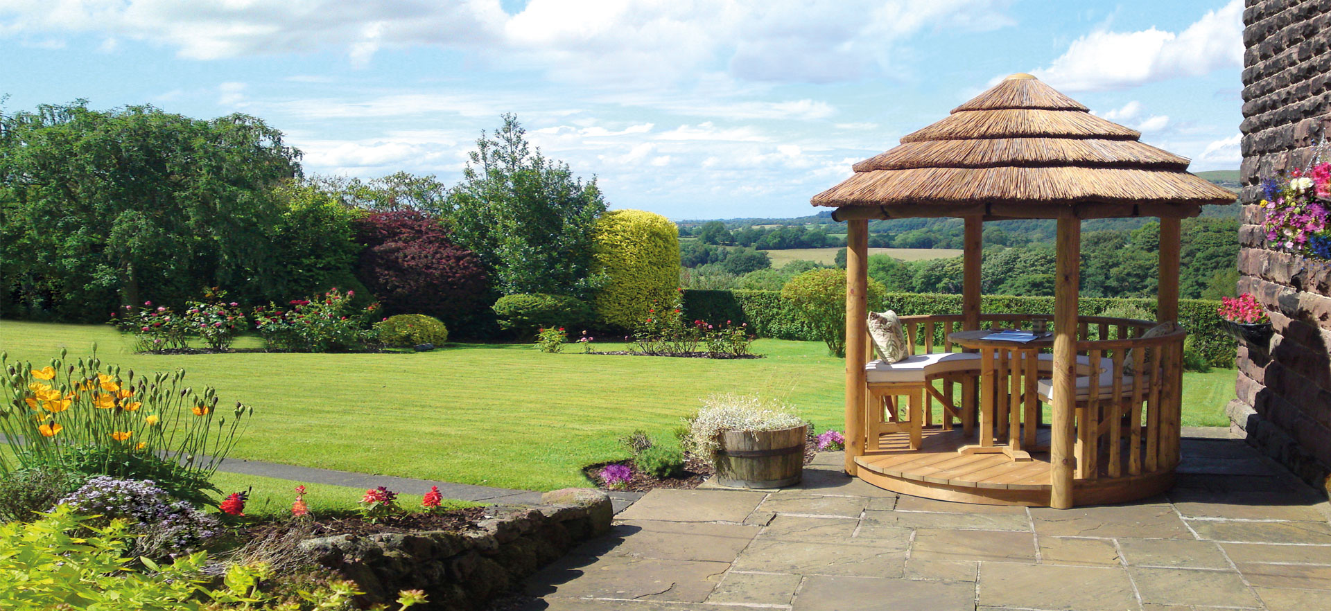 2 metre thatched roof gazebo overlooking large open plan garden and fields