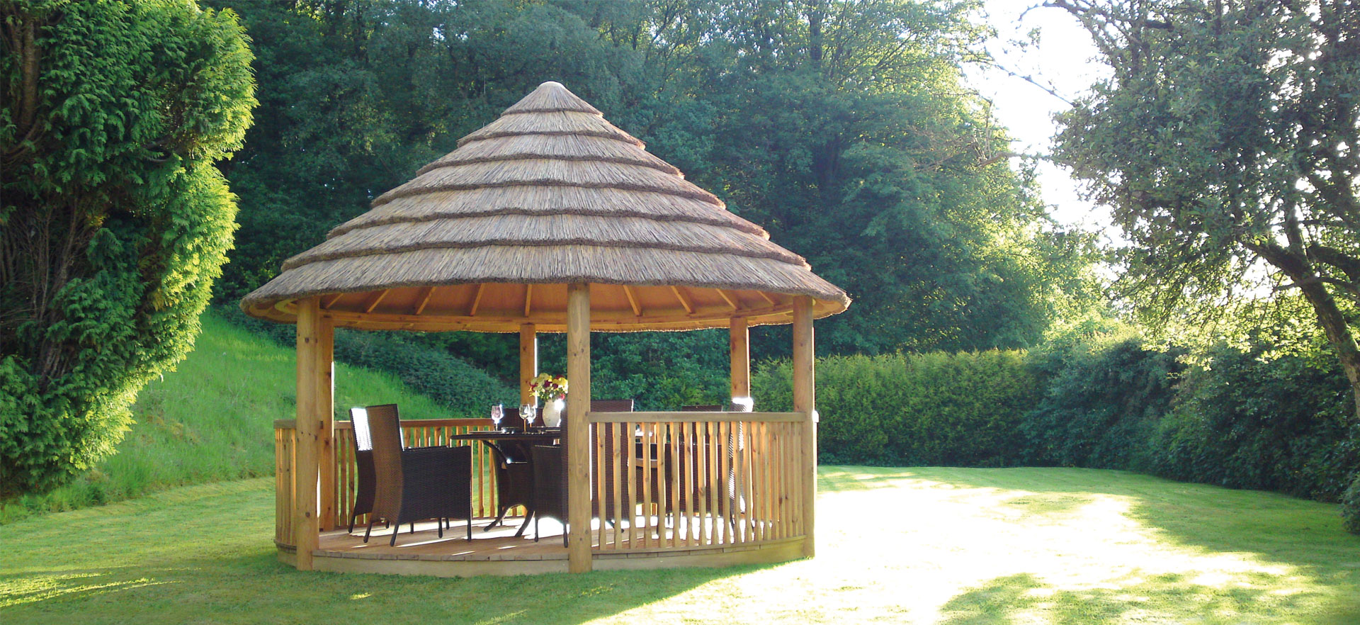 3.5 metre luxury thatched gazebo in cove of grass and foliage