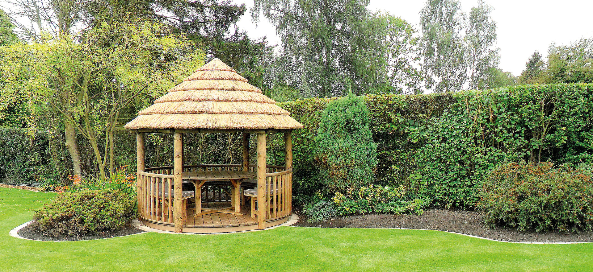 3 metre thatched roof gazebo surrounded by greenery