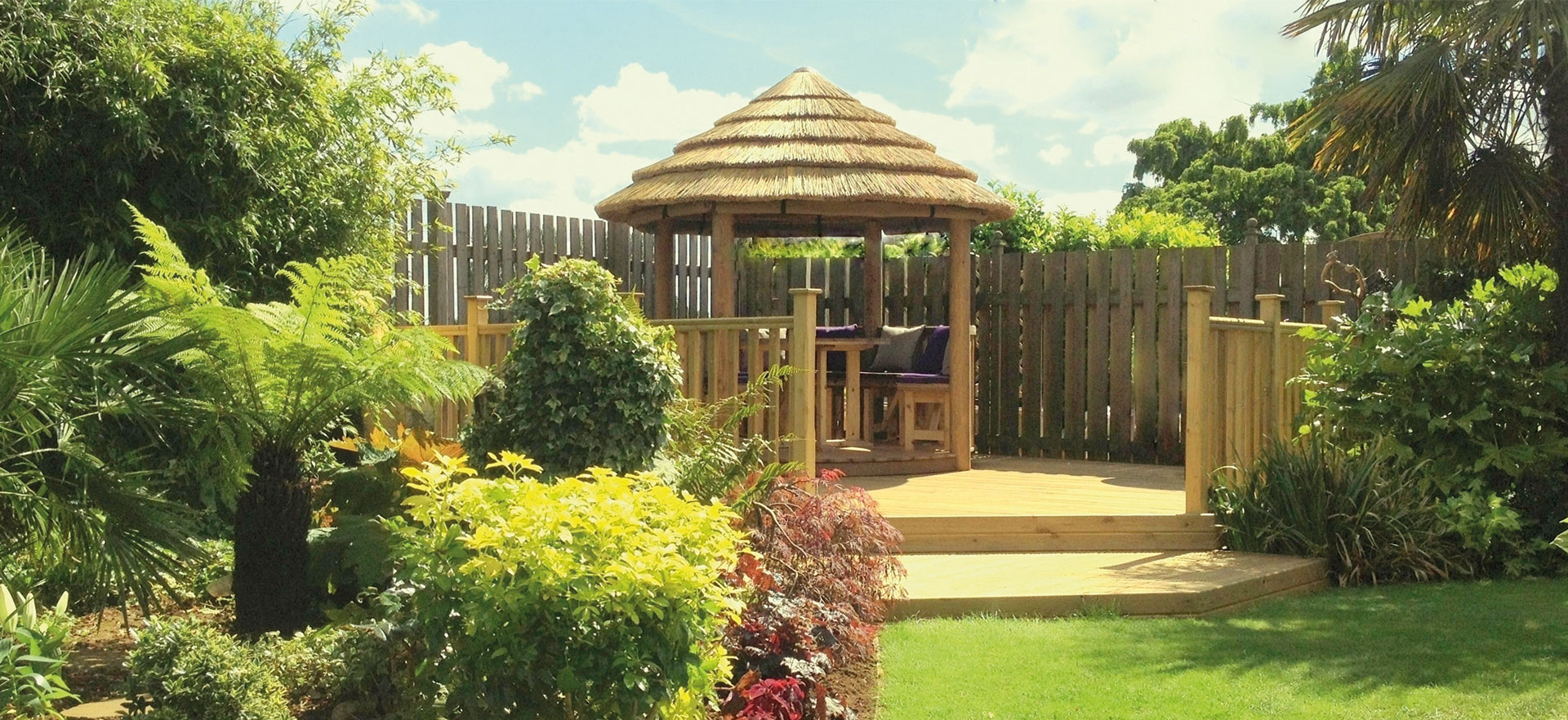 2.5 metre thatched roof gazebo on raised deck in garden