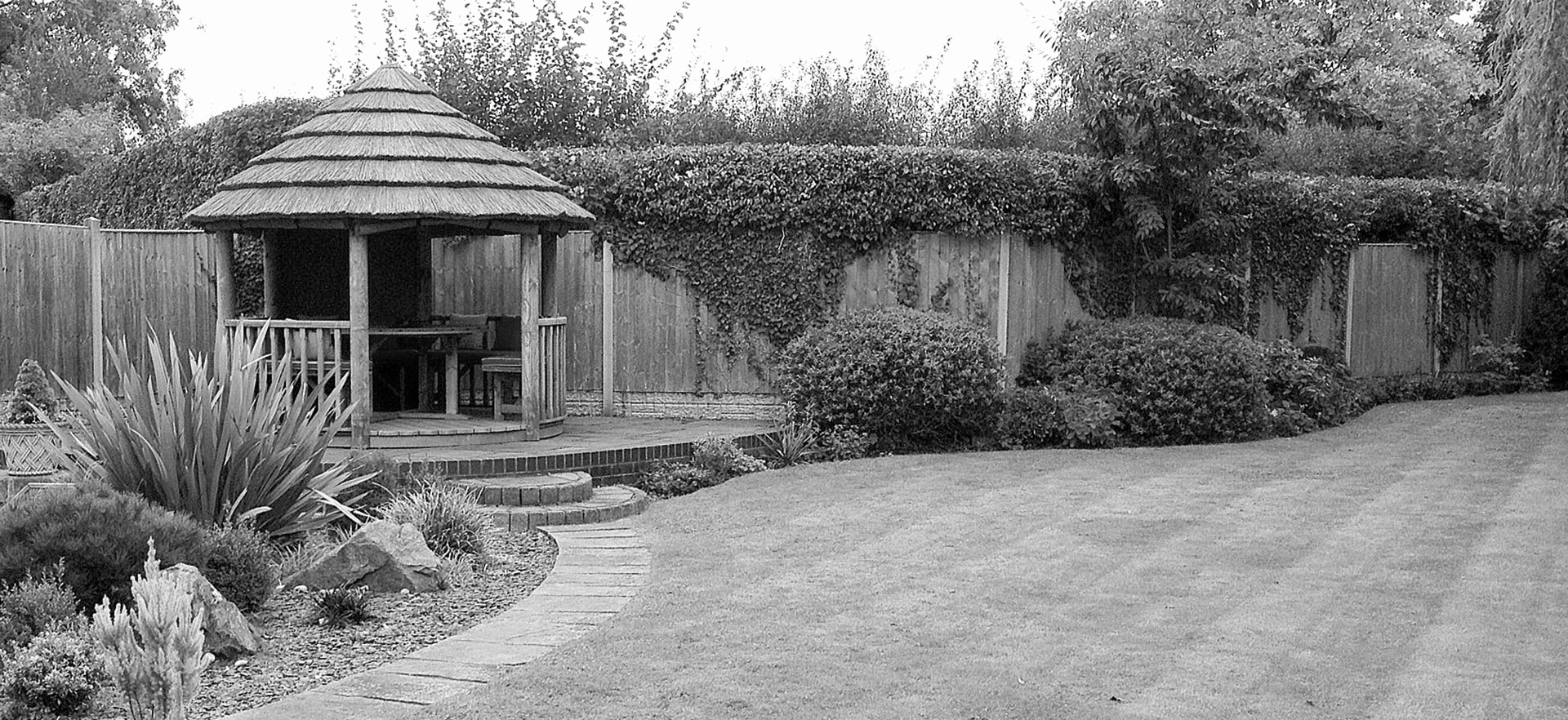 black and white image of 3 metre thatched gazebo in corner of garden