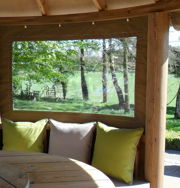 Inside a thatched gazebo looking as closed canvas panelling