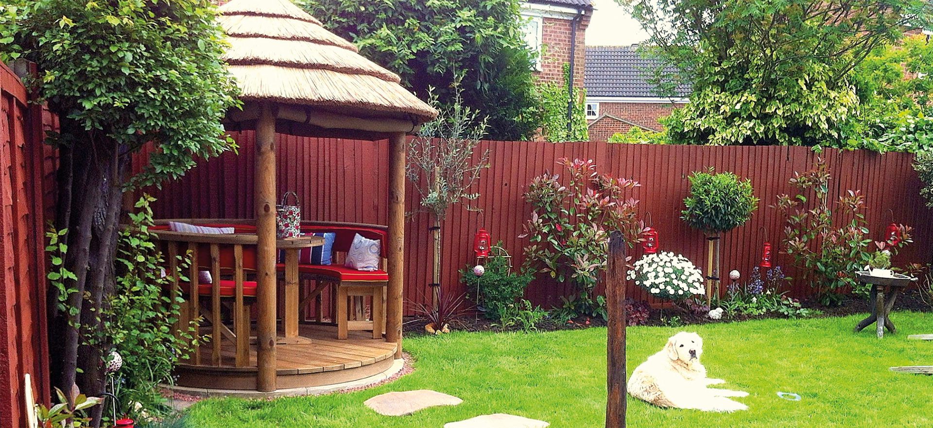 2 metre thatched gazebo in corner of small garden