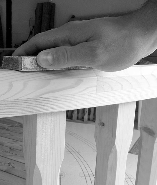 Black and white image of hand sanding some wood