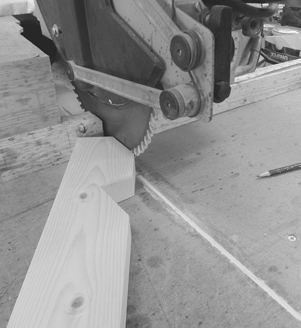 Black and white image of circular saw cutting through wood