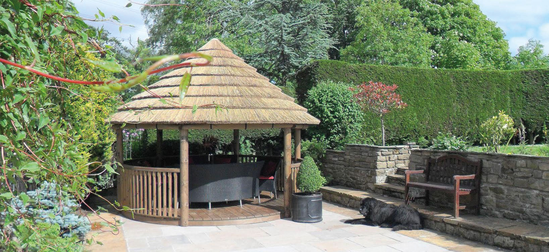 4 metre thatched roof gazebo in enclosed garden space